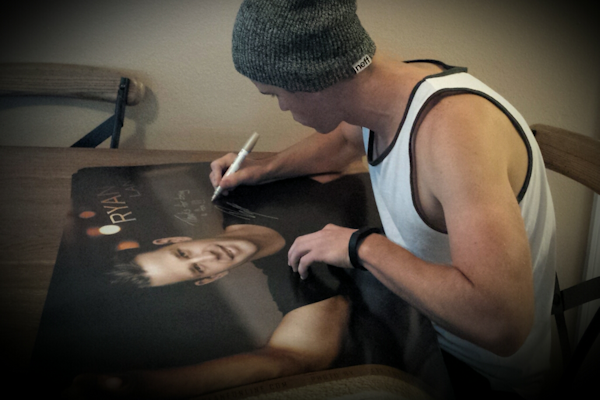 Actor Ryan Lane autographing his new posters